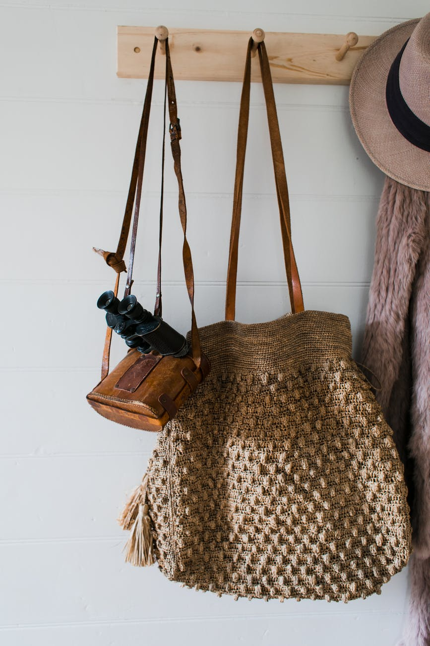 hanger with clothes and bag in light room