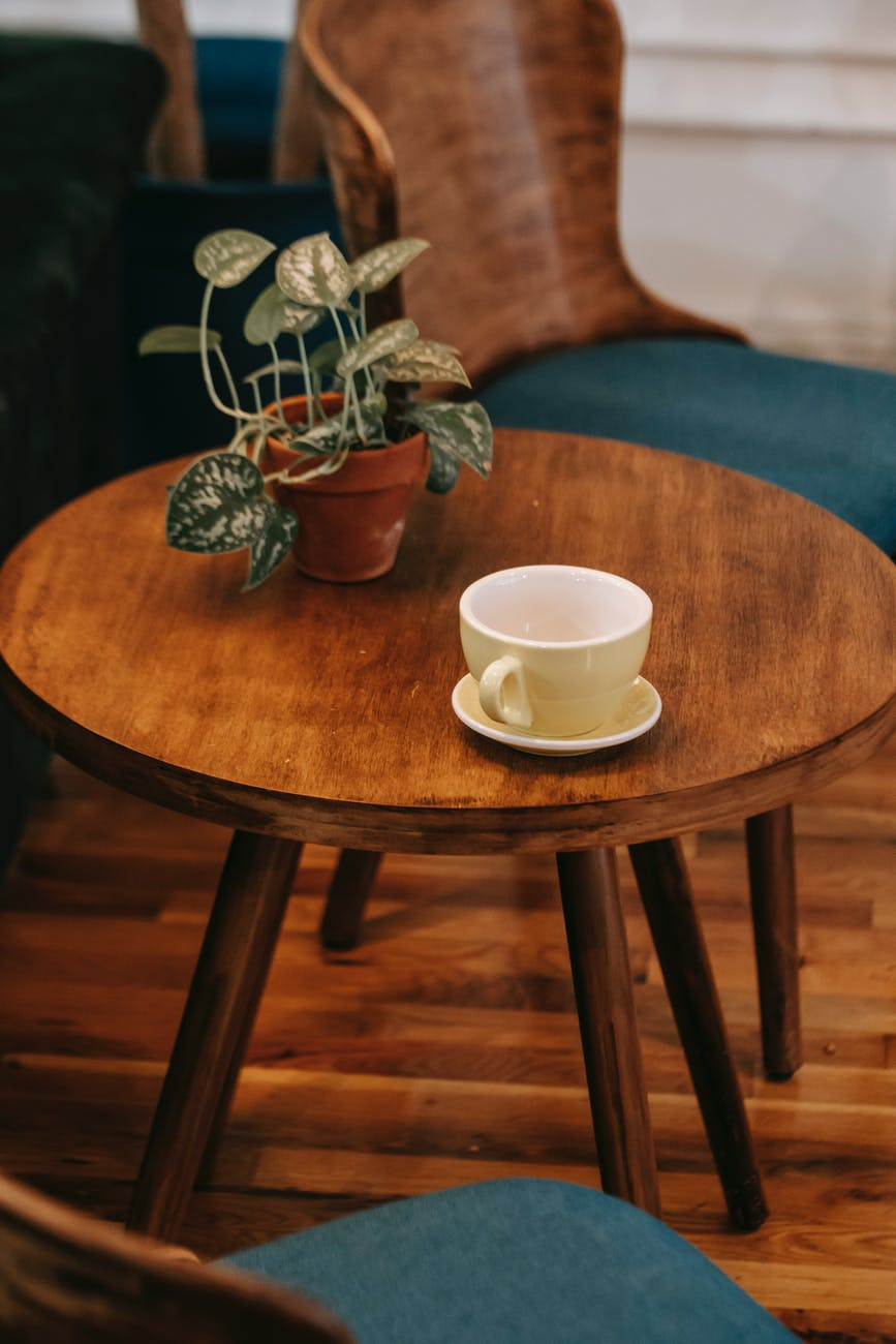stylish wooden table with ceramic cup and potted flower in cozy cafe