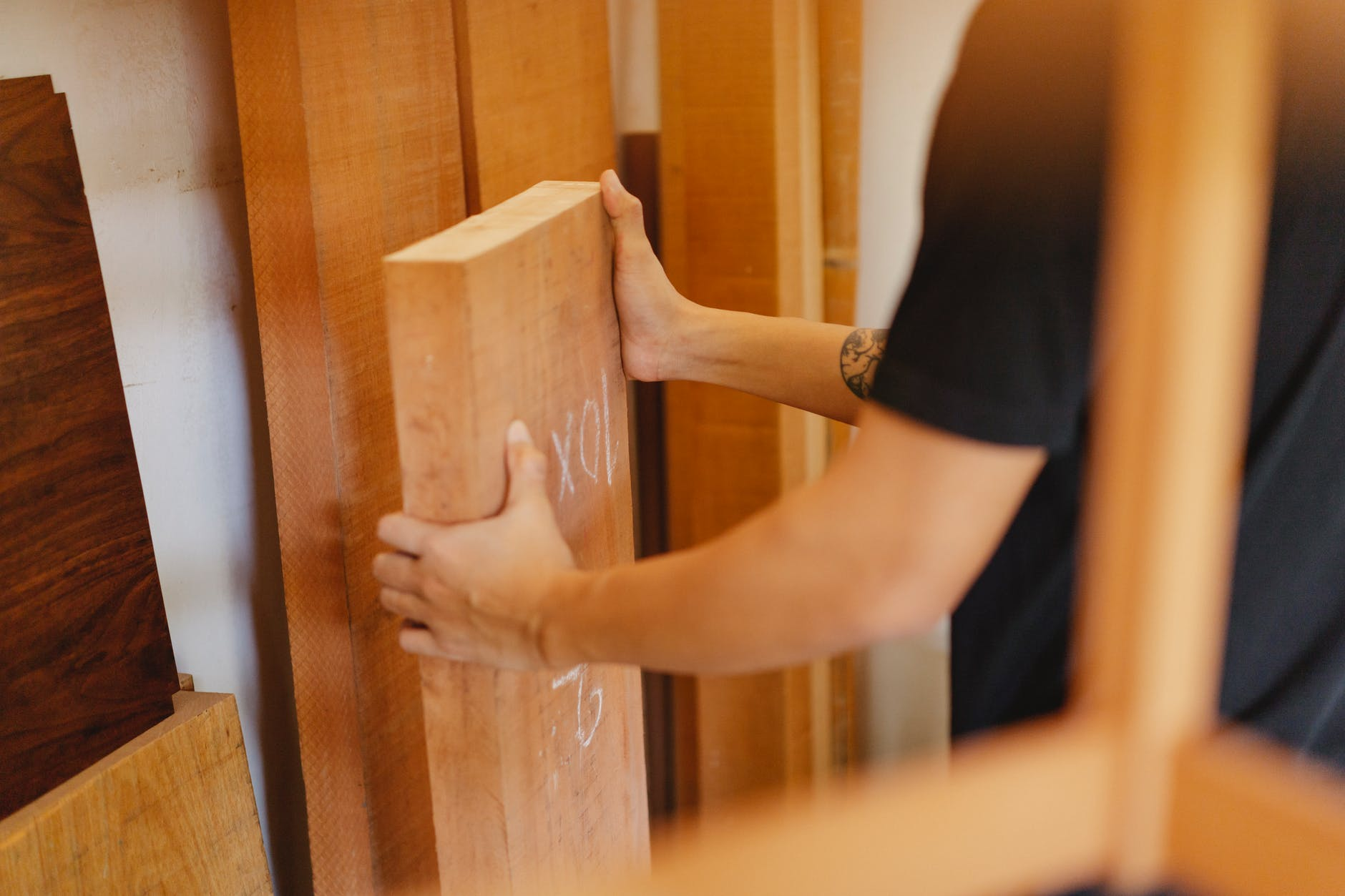 man picking wooden plank from store